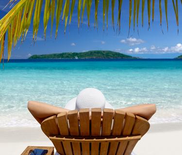 woman sunbathing in a teak chair on a beautiful Caribbean beach